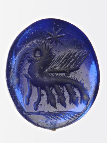 Blauw glazen gem uit de vroege Middeleeuwen met vijfkoppig monster, gevonden in Apeldoorn. Foto: Rijksmuseum van Oudheden, Leiden