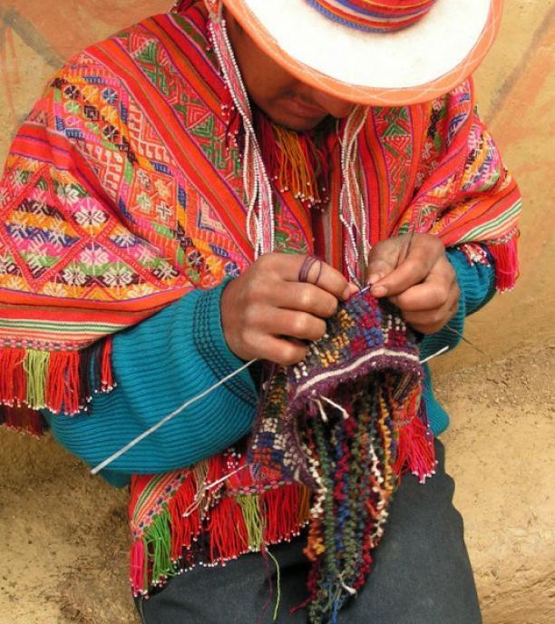 Een man van Accha Alta die een gebobbelde chullo breit. Bron: Clothroads.com.