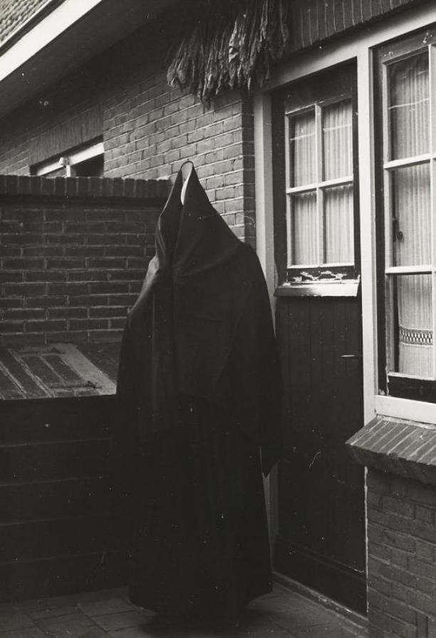 Vrouw in de streekdracht uit Huizen, met een 'regenkleed' voor een begrafenis, 1945, collectie Nederlands Openluchtmuseum.