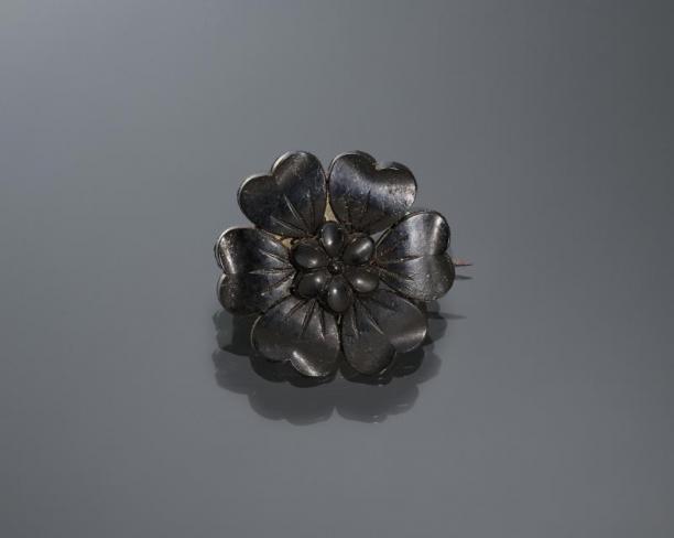 Zwarte broche, gedragen door een vrouw uit Kampen tijdens de zware rouw. De bloem is gemaakt van kunststof, als imitatie van git. Collectie Nederlands Openluchtmuseum.