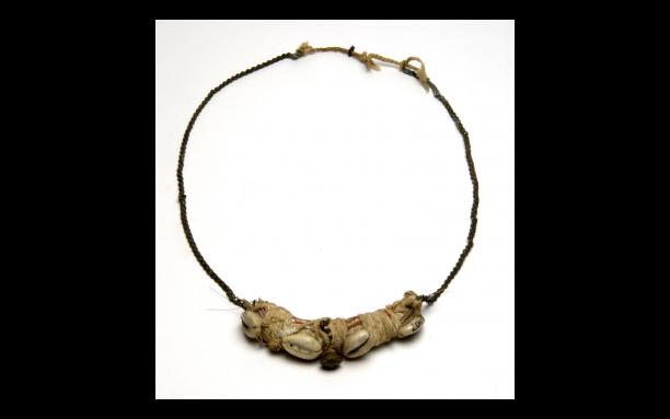 Halssieraad / amulet, messing ketting, buidel met vermoedelijk een 'obia', met katoen omwikkeld en ingesmeerd met pemba doti, papa moni en messing belletje. Veertjes uiteinden zijn verdwenen. Suriname, Marron, voor 1926, collectie Wereldculturen