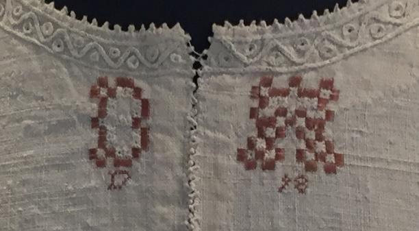 Detail van de initialen op het doodshemd.