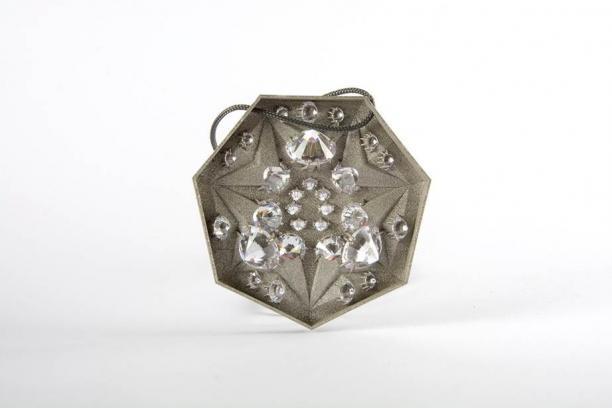 Achterkant van Badge 4 van Adam Grinovich, halsketting met zeskantige hanger van staal met zirkoniastenen, 2017, collectie CODA Apeldoorn.