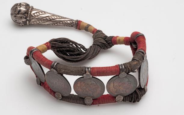 Mannensieraad, zilver, zes zilveren munten, katoenvezel, Suriname, Hindostaans, voor 1900. Te zien in De Grote Suriname-tentoonstelling. Collectie Nationaal Museum van Wereldculturen